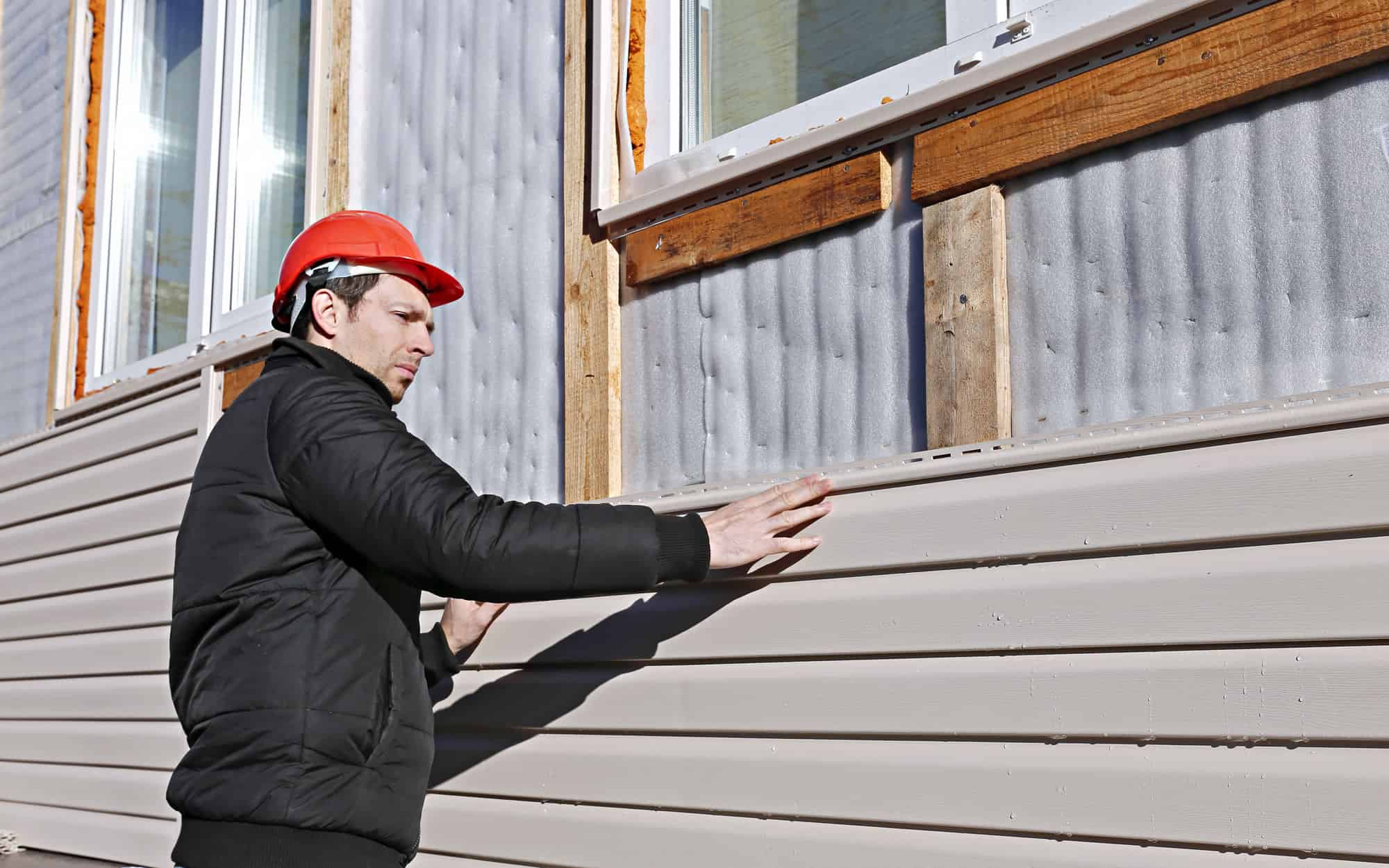 Triangle Painting employee repairing house siding
